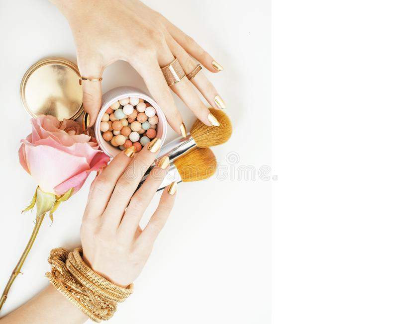 Mains de femme avec la manucure d'or et beaucoup des anneaux tenant des brosses, photographie stock libre de droits
