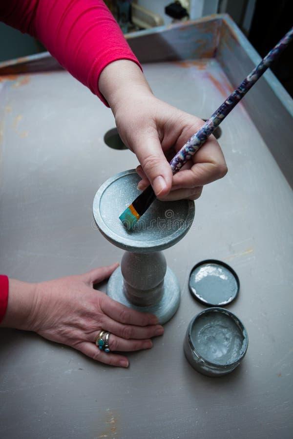 Mains de femme avec la peinture de brosse avec candlestic en bois de peinture crayeuse photographie stock