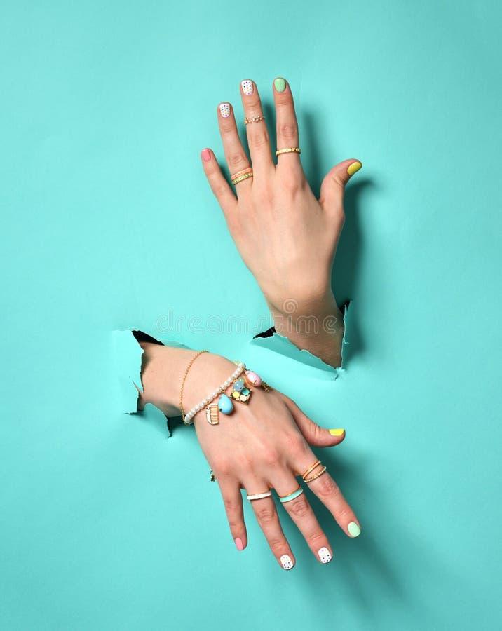 Mains de femme avec le vernis à ongles de modèle et le silve blancs roses jaunes photo stock