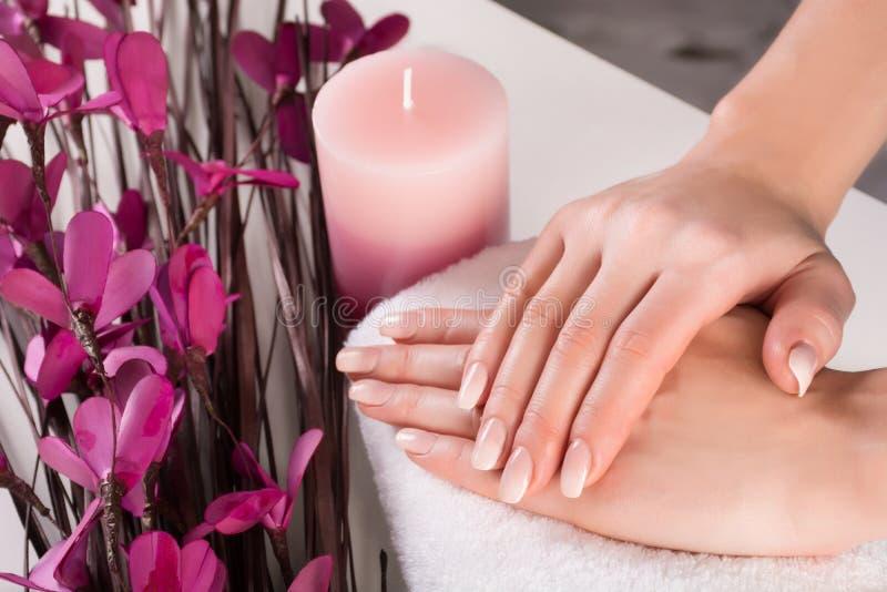 Mains de femme avec les clous français d'Ombre et fleur pourpre avec la bougie aromatique dans la station thermale photographie stock