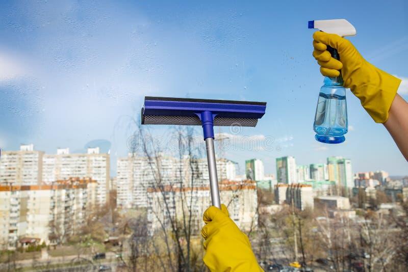 Mains de femme avec les gants en caoutchouc jaunes tenant l'outil de nettoyage de verre de fenêtre et la bouteille de jet avec le photos libres de droits