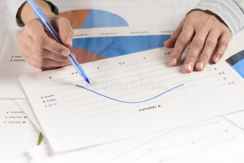 Mains de femme d'affaires analysant des statistiques financières photo stock