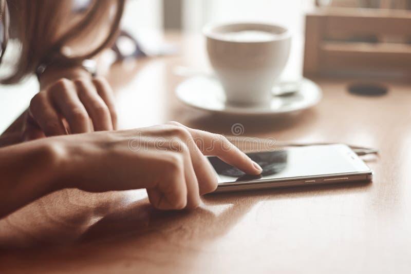 Mains de femme d'affaires utilisant le téléphone et la tasse de café intelligents photographie stock libre de droits