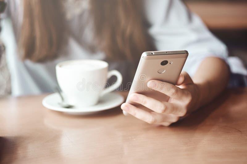 Mains de femme d'affaires utilisant le téléphone et la tasse de café intelligents photos libres de droits