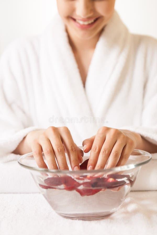 Mains de femme dans le bol en verre avec de l'eau sur la serviette blanche images stock