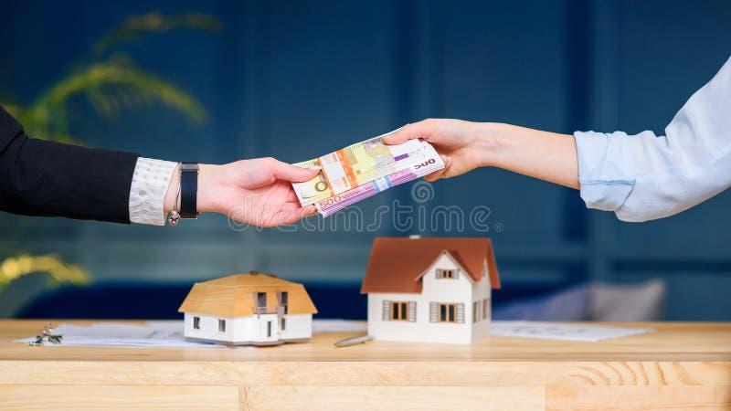 Mains de femme donnant l'argent pour la nouvelle maison, à plat à l'agent immobilier image libre de droits