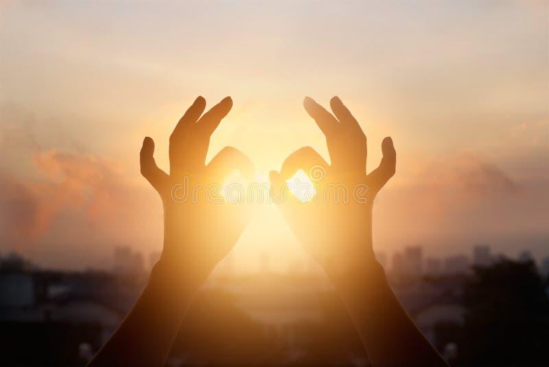 Mains de femme en position de lotus du yoga et de la méditation, silhouette sur le coucher du soleil de nature photographie stock libre de droits
