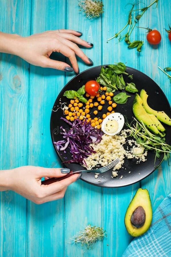 Mains de femme et cuvette saine de déjeuner de vegan Cuvette de Bouddha de Vegan Les légumes et les écrous en Bouddha roulent sur images libres de droits