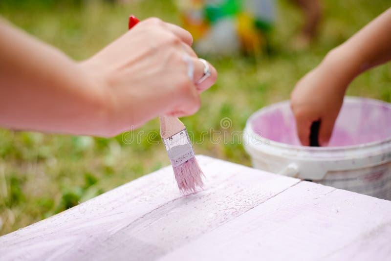 Mains de femme et d'enfant peignant la planche dans le rose image stock