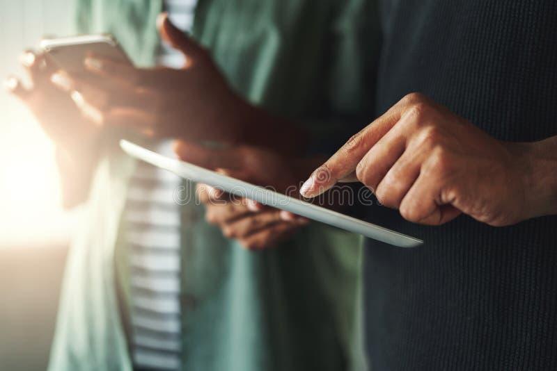 Mains de femme et d'homme avec le PC de smartphone et de comprim? image libre de droits