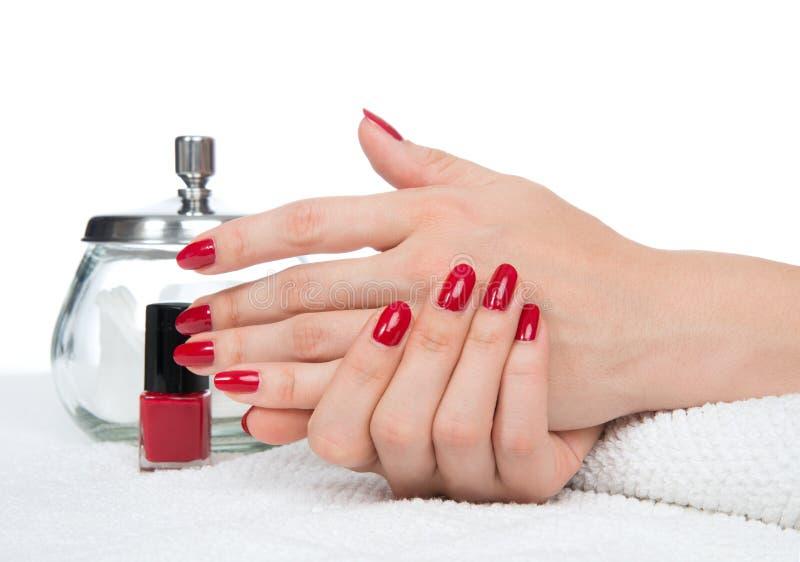 Mains de femme faisant des ongles de rouge de manucure photographie stock