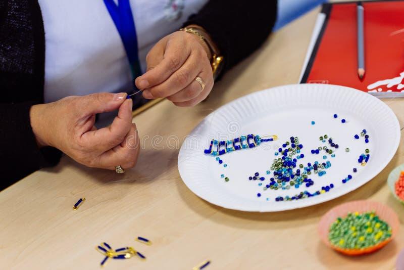 Mains de femme faisant le bracelet de perle photo libre de droits