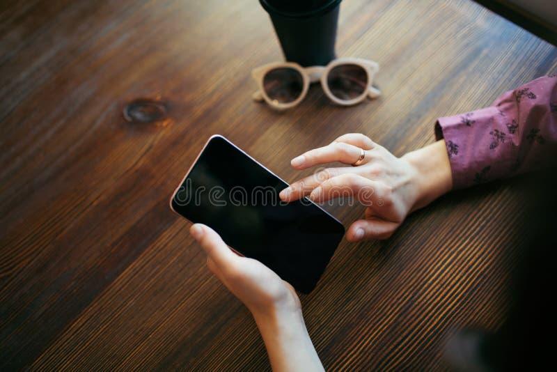 Mains de femme mettant en rouleau l'écran du téléphone portable images libres de droits