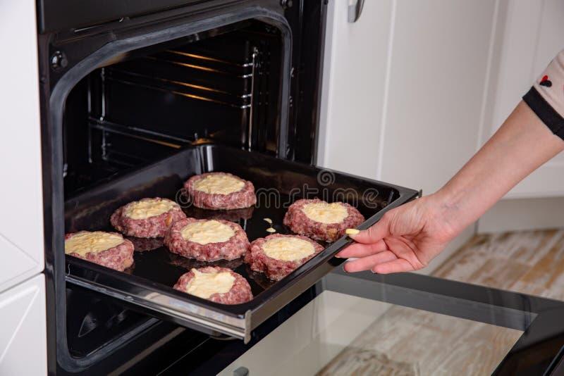 Mains de femme mettant le plateau de cuisson avec des côtelettes ou des boulettes de viande et dans le four photo libre de droits