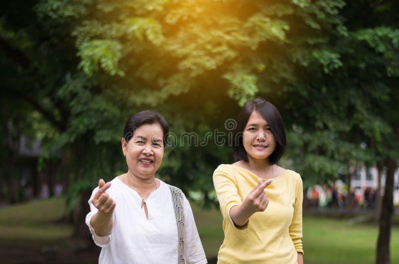 Mains de femme montrant le mini coeur et détendre au parc public pendant le matin ensemble, heureux asiatiques et souriant, pensé photographie stock libre de droits