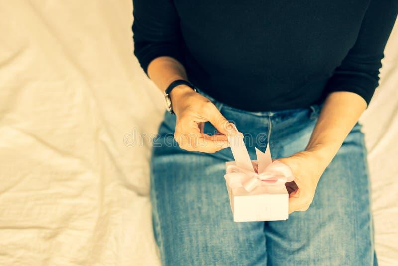 Mains de femme ouvrant des présents de valentine dans la couleur de processus croisée photos libres de droits