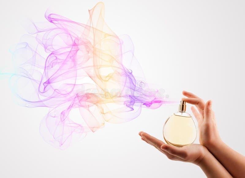 Mains de femme pulvérisant le parfum photos libres de droits