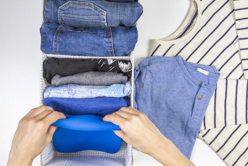 Mains de femme rangeant des vêtements d'enfants dans le panier Stockage vertical d'habillement, rangeant, concept de nettoyage de photo libre de droits