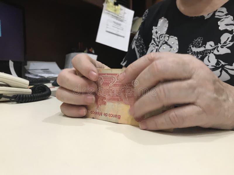 Mains de femme saisissant une pile de 100 billets de banque de peso mexicain image libre de droits