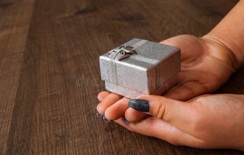 Mains de femme sur la table en bois donnant le boîte-cadeau photos stock