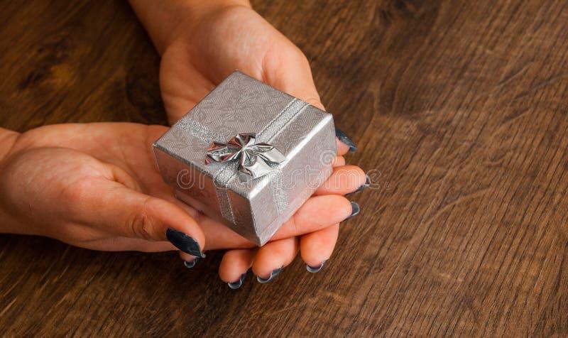 Mains de femme sur la table en bois donnant le boîte-cadeau photo libre de droits