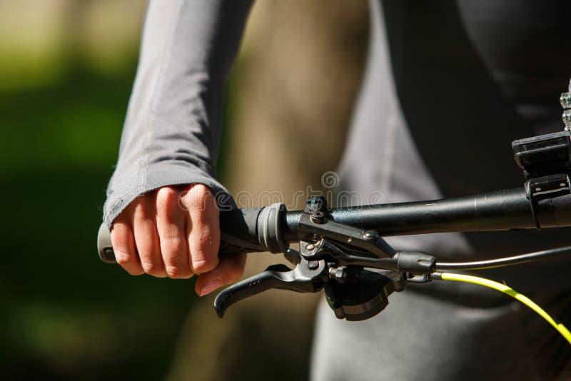 Mains de femme sur le vélo moderne de sport photo stock