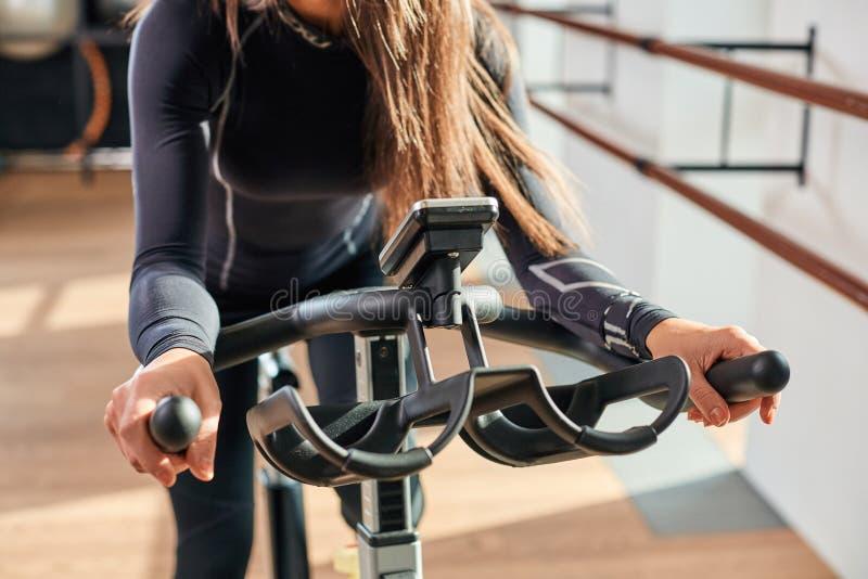 Mains de femme sur un vélo stationnaire de barre le gymnase images libres de droits