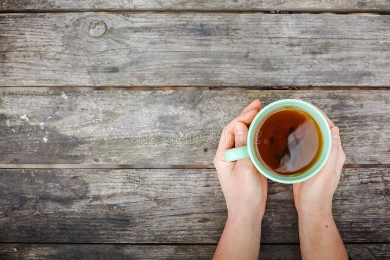 Mains de femme tenant la tasse de la boisson chaude photographie stock