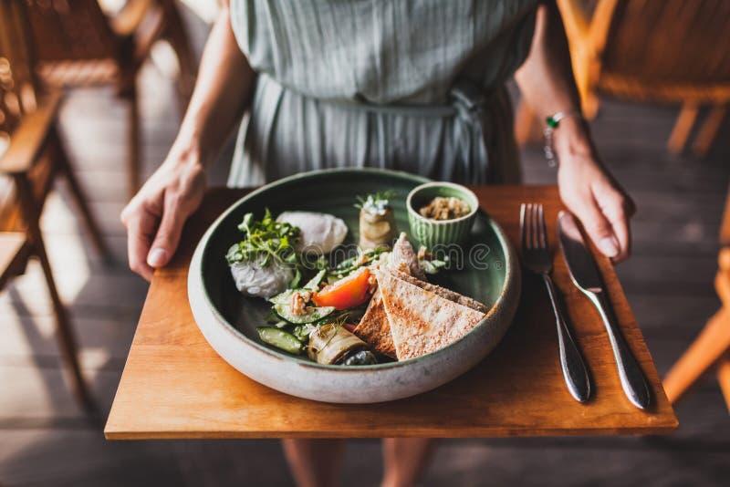 Mains de femme tenant le plat avec le petit déjeuner oriental photographie stock libre de droits