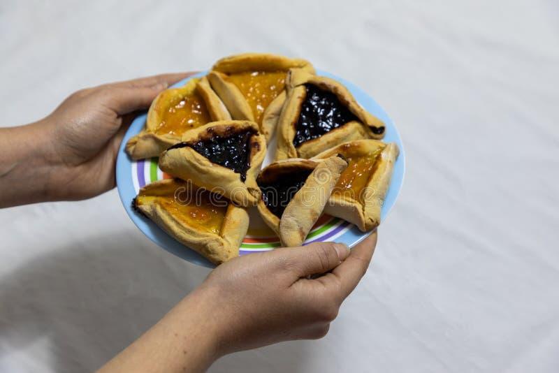 Mains de femme tenant le plat color? avec des biscuits de Purim de hamantash d'abricot et de myrtille photographie stock libre de droits
