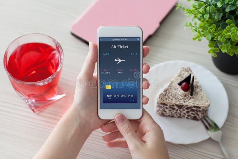 Mains de femme tenant le téléphone avec le billet d'avion en ligne en café photographie stock