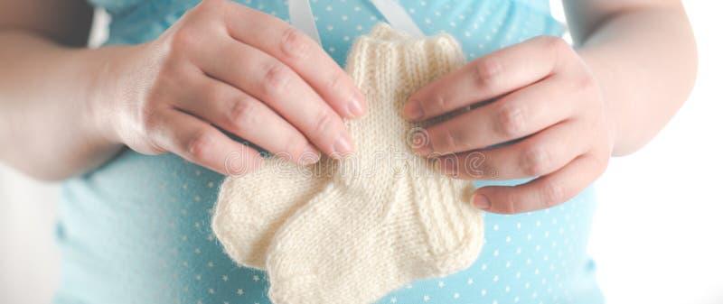 Mains de femme tenant les chaussettes chaudes pour l'enfant photographie stock