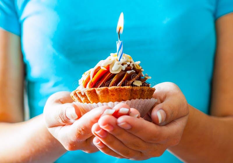 Mains de femme tenant un petit gâteau d'anniversaire de chocolat avec le buttercream et la bougie photo libre de droits
