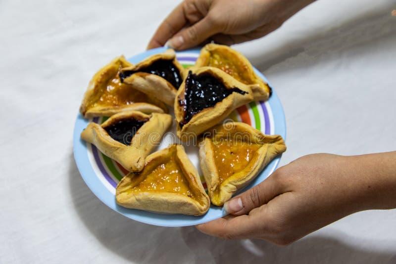 Mains de femme tenant un plat color? avec des biscuits de confiture de myrtille et d'abricot de Hamantash Purim sur la nappe blan photographie stock