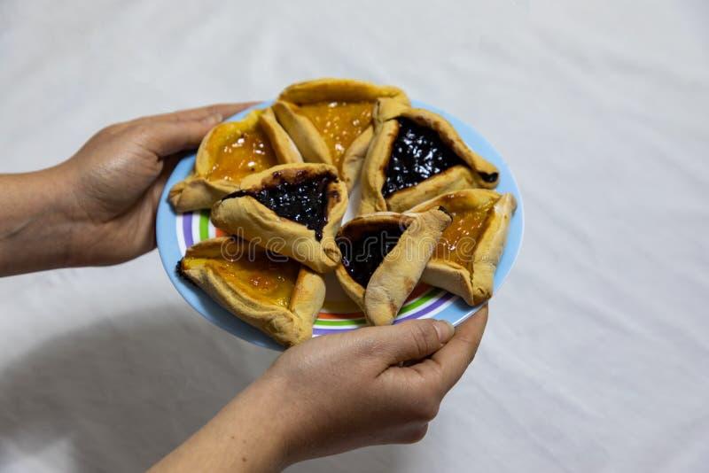 Mains de femme tenant un plat color? avec des biscuits de confiture de myrtille et d'abricot de Hamantash Purim sur la nappe blan photos stock