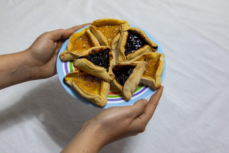 Mains de femme tenant un plat color? avec des biscuits de confiture de myrtille et d'abricot de Hamantash Purim sur la nappe blan images stock