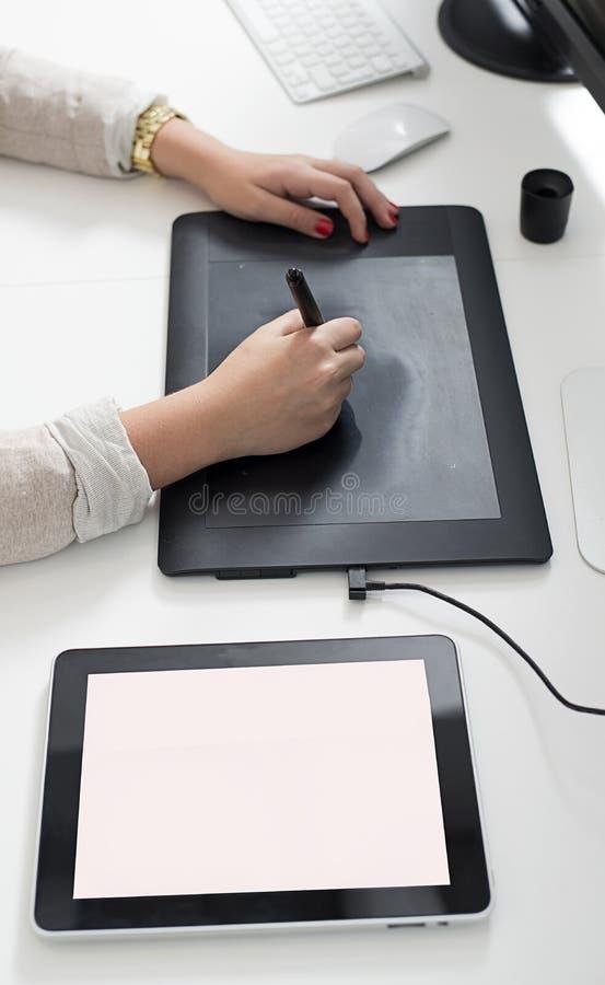 Mains de femme utilisant une tablette graphique image stock