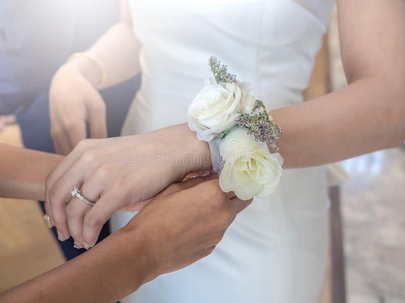 Mains de femmes attachant vers le haut du bracelet rose blanc de fleur à la jeune mariée photos stock