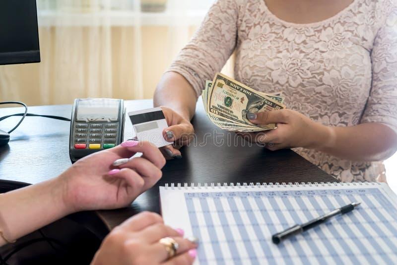 Mains de femmes avec carte de crédit, terminal de paiement et dollars photo stock