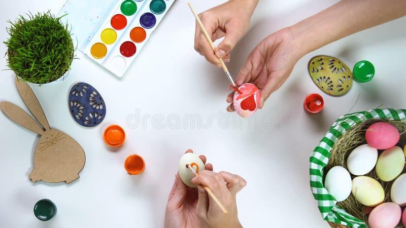 Mains de femmes décorant des oeufs sur la table, traditions de Pâques, connexion de famille images stock