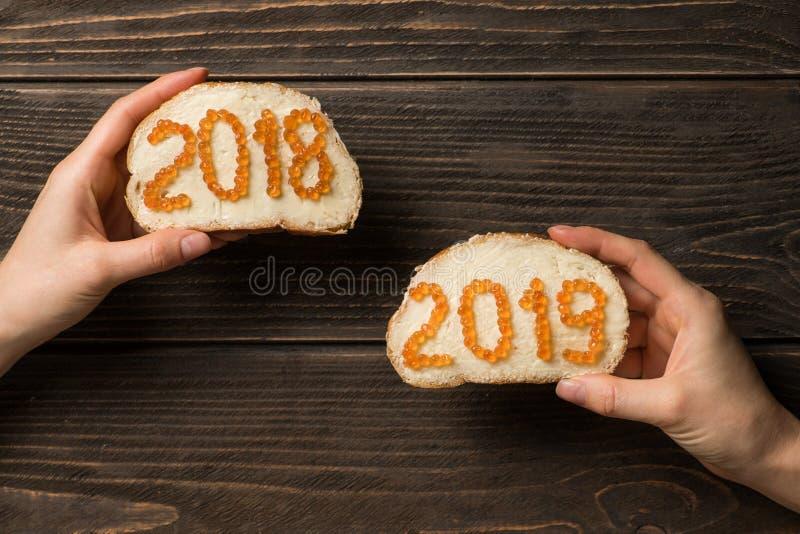 Mains de femmes tenant deux sandwichs avec le caviar rouge sous forme de 2018 et 2019 nombres photos stock