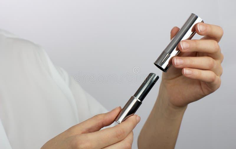 Mains de fille avec le rouge à lèvres argenté images libres de droits