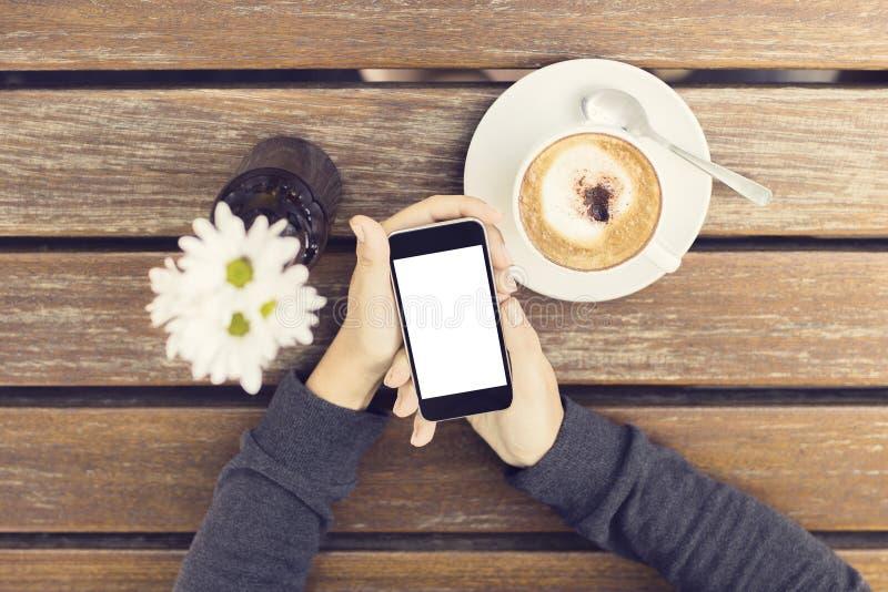 Mains de fille avec le smartphone vide, la tasse de café et les fleurs photos libres de droits