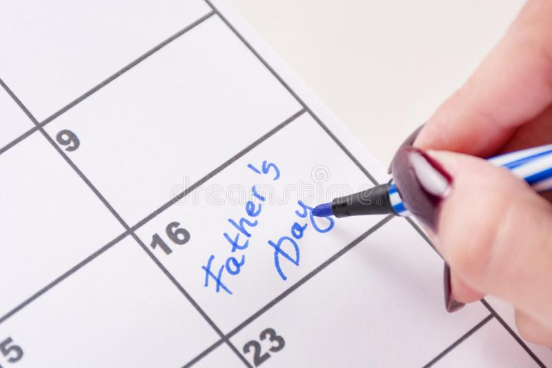 Mains de fille avec le stylo senti bleu écrivant le jour de pères de mots dans le calendrier image libre de droits