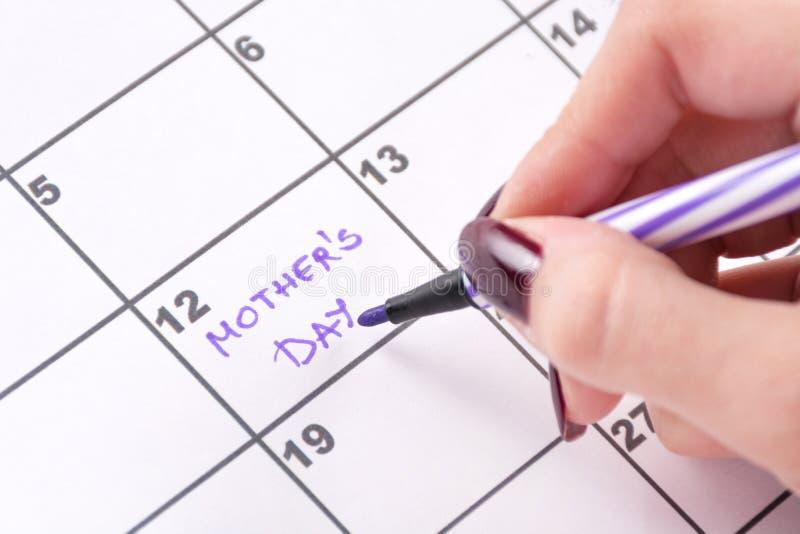 Mains de fille avec le stylo senti pourpre écrivant dans le jour de mères de mots de calendrier photos stock