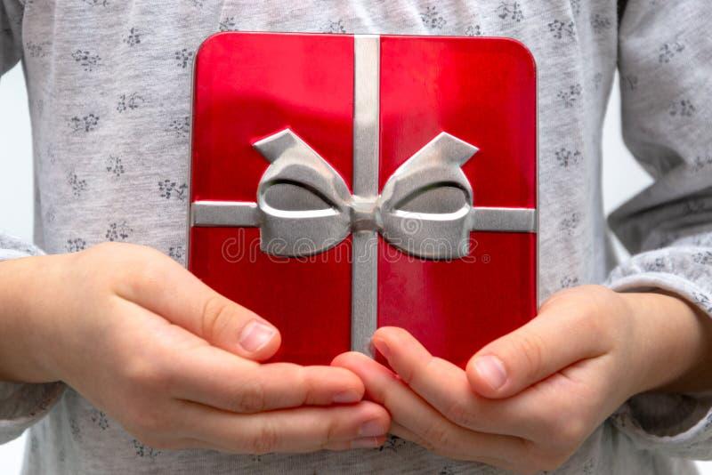 Mains de fille montrant le cadeau dans une boîte, tenant le boîte-cadeau rouge avec l'arc au-dessus du fond de vacances images libres de droits