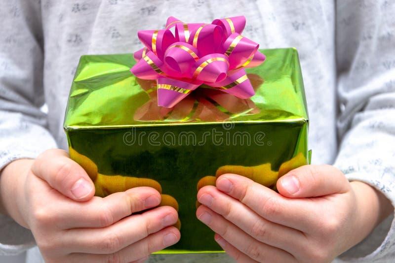 Mains de fille montrant le cadeau dans une boîte, tenant le boîte-cadeau vert avec l'arc au-dessus du fond de vacances photo libre de droits