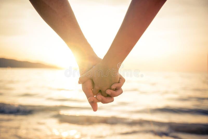 Mains de fixation de couples au coucher du soleil image stock