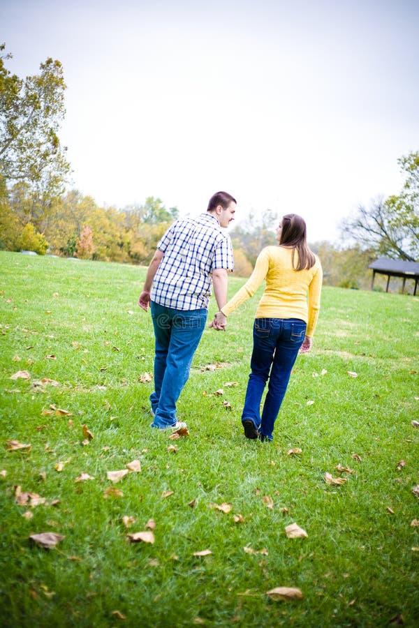 Mains de fixation de couples marchant dans un domaine photos stock