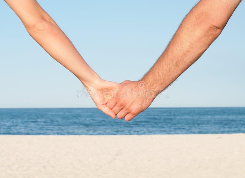 Mains de fixation de couples sur la plage photographie stock libre de droits